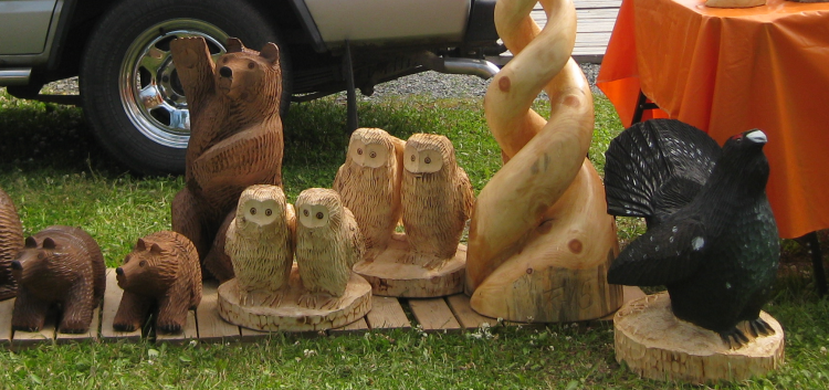 In the picture are wooden carved animals on a lawn.