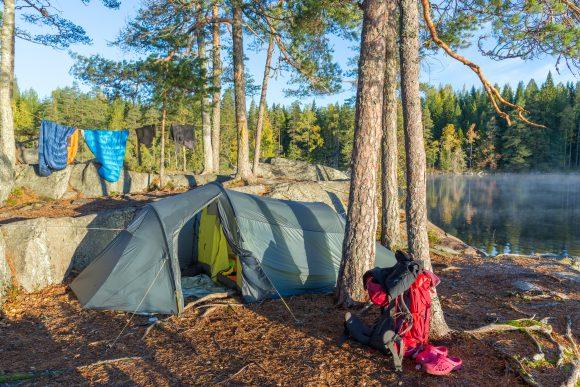 Tyhjä teltta mäntymetsässä järven rannalla. Teltan edessä on rinkka.