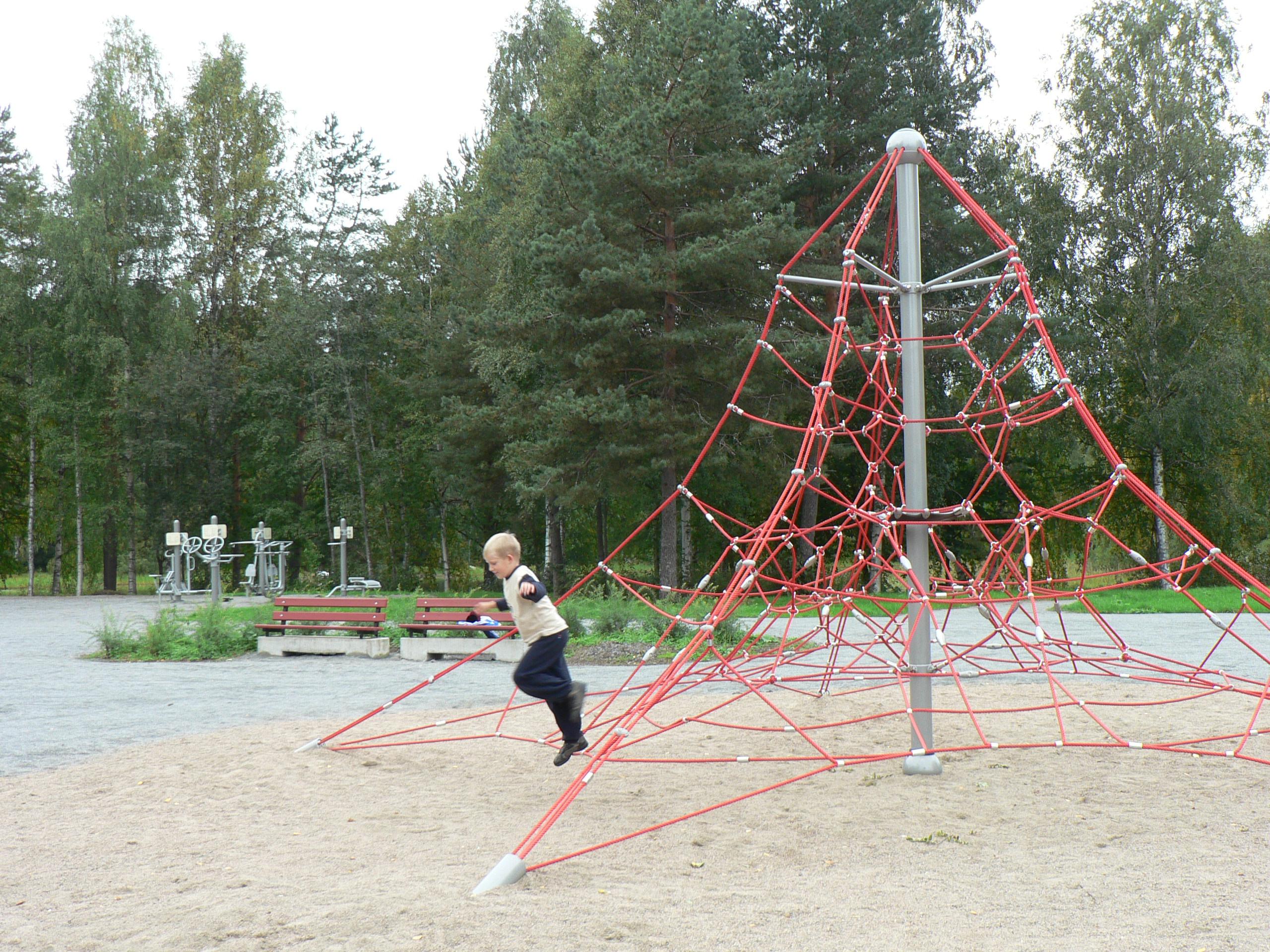 Puistossa sijaitseva lasten kiipeilyteline ja poika
