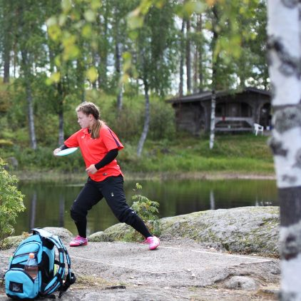 Pelaaja heittää frisbeetä järven rannalla